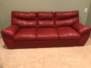 A red leather couch in a room with green walls and unfinished floors