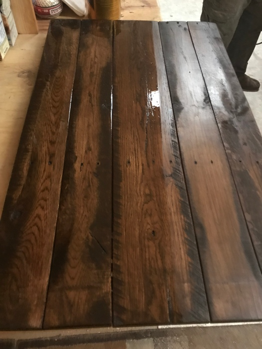 Reclaimed oak pallet wood stained a dark walnut color, and half painted with polyurethane.