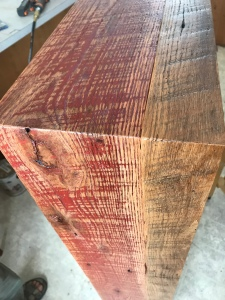 The edge of a cabinet made out of Reclaimed oak with old red paint on it, showing the waterfall effect.