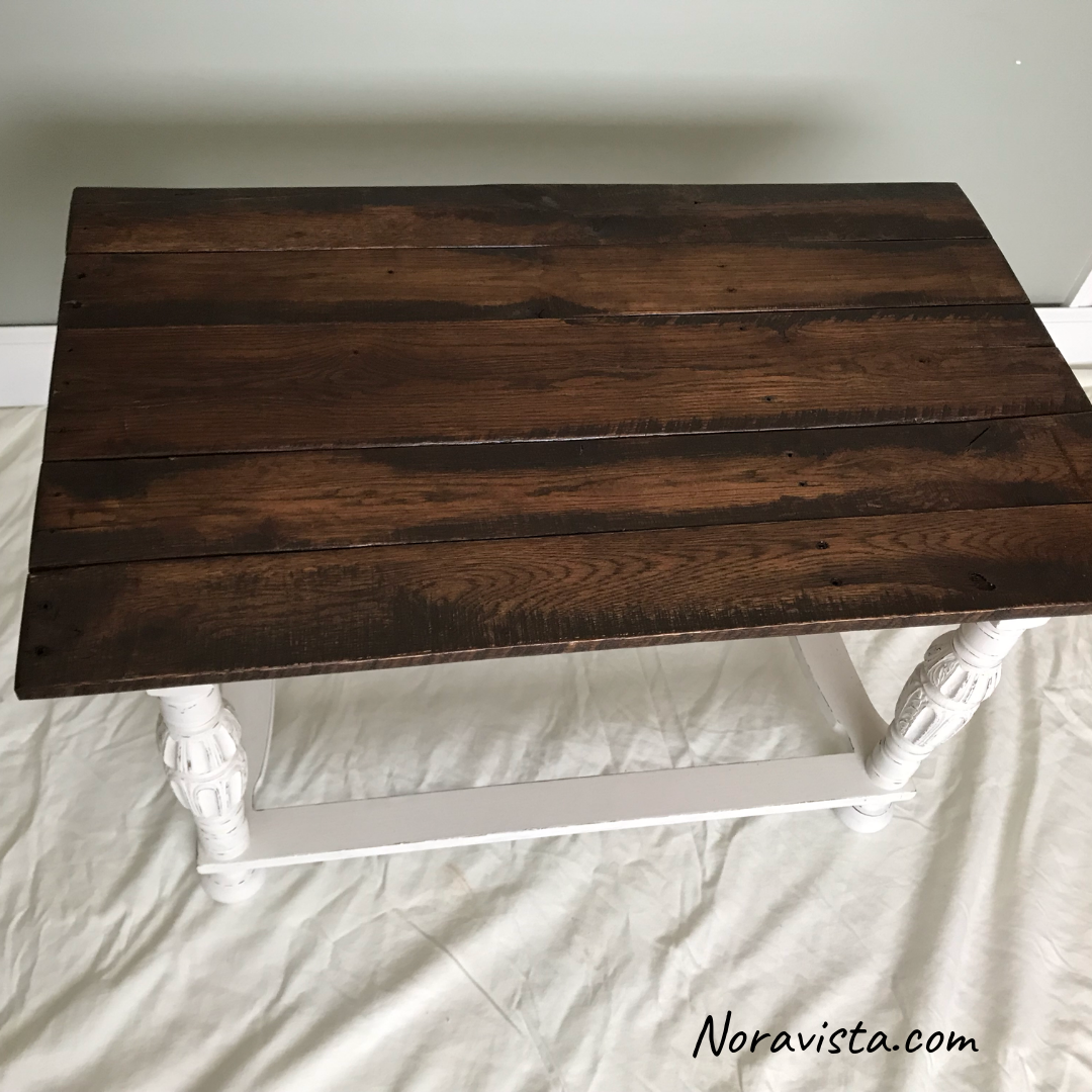 A reclaimed oak table top stained a dark walnut color and protected with polyurethane, on a white painted and distressed base.