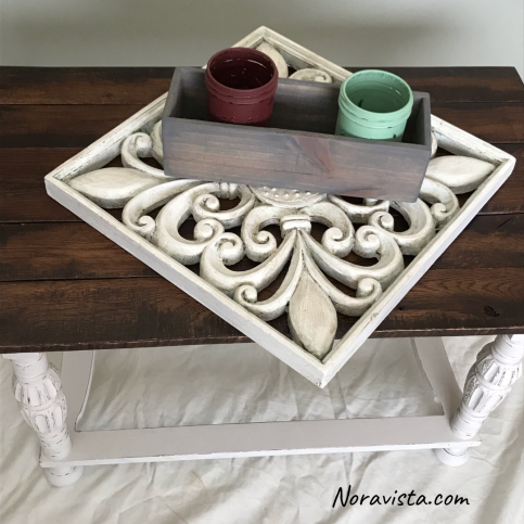 Painted mason jars in a gray box sitting on top of a decorative fleur de lis art piece on top of a solid oak table