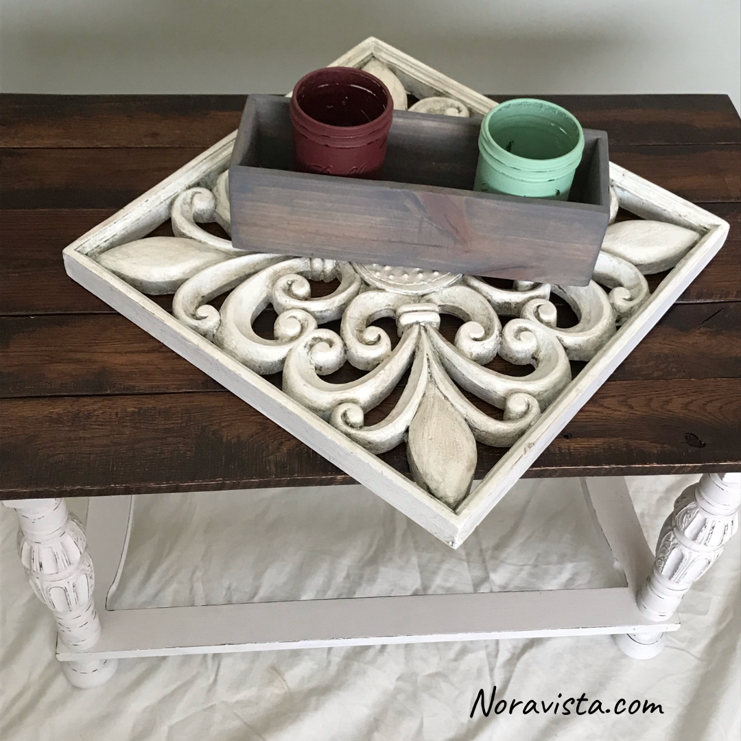 A reclaimed oak table top stained a dark walnut color and protected with polyurethane, on a white painted and distressed base with decor displayed on the top which includes painted mason jars in a gray stained box on top of a fleur de lis wall art piece.