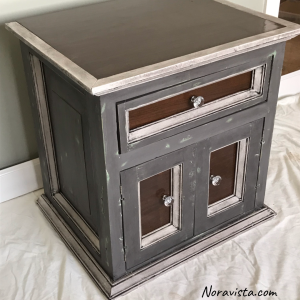 A small gray cabinet with white molding that has been waxed black and walnut top with walnut door and drawer panels and crystal pulls