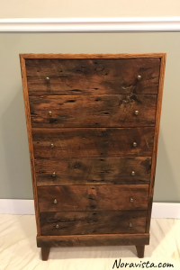 A midcentury Modern cabinet made from reclaimed oak barn wood featuring old nail holes, knots and saw tooth marks with the drawer fronts cut sequenced, and tiny brass knobs on the drawers for pulls