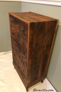 A midcentury modern waterfall cabinet side made from reclaimed oak barn wood featuring old nail holes and knots and saw tooth marks