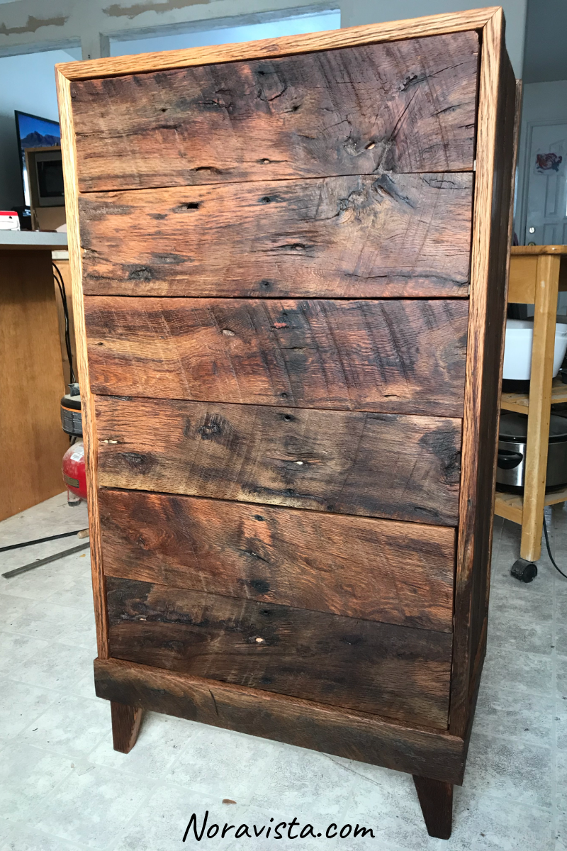 a medcentury Modern style cabinet that has sequenced drawer fronts from reclaimed oak barn wood with old nail holes, saw tooth marks and knots and the natural light showing the shimmering colors throughout the features
