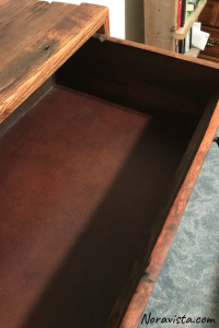 The top drawer of a cabinet pulled out to reveal brown leather lining on the bottom of the drawer