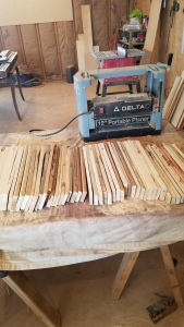 A stack of Pine reclaimed pallet wood sitting in front of a delta planer on a table in a workshop