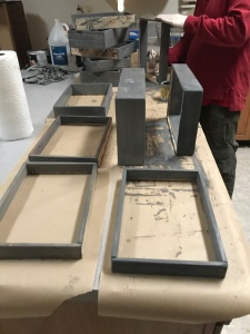 Drawer box sides stained gray sitting on a table on top of wax paper while drying and a man applying stain to one of them