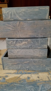 Drawer box sides stained gray with starburst patterns in the stain, stacked upon each other