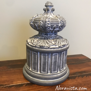 A round tall box with Raised French decorations all around it painted gray and waxed with white wax