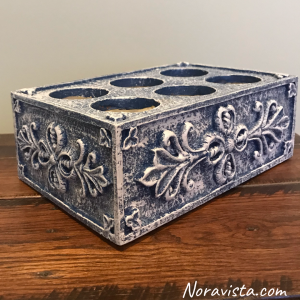 A blue and white box with floral raised panels and six holes in the top
