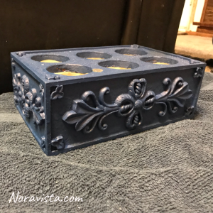A blue box with floral raised panels and six holes in the top