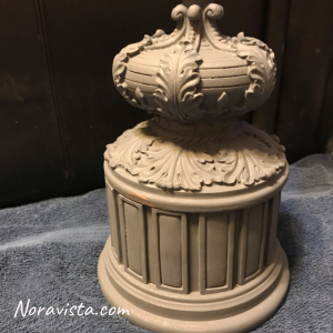 A round tall box with Raised French decorations all around it painted gray