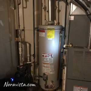 A utility room with a furnace, water heater and water pump
