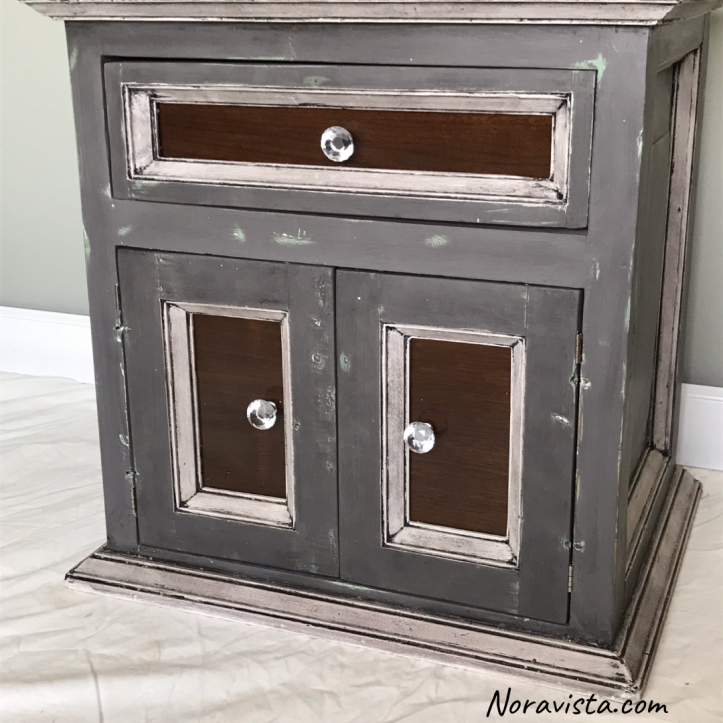 A small cabinet painted gray and white, waxed black and has walnut accents