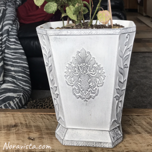 A white painted planter with gray dry brushed highlights sitting on an oak bench