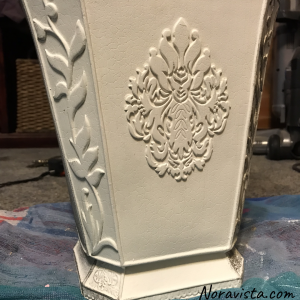 A medium sized planter with leaf designs on the edges and a French decorative piece in the center, painted white