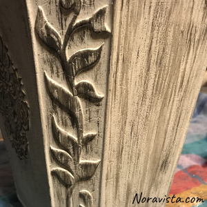 An up close view of a decorative planter in white with wet streaks of gray painted on it