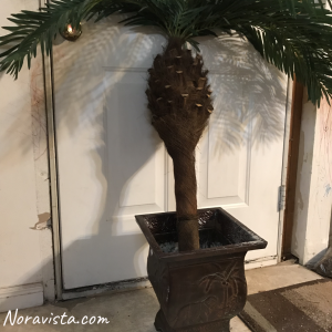 A metal bohemian planter with an elephant and monkey on the sides with a fake palm tree in it