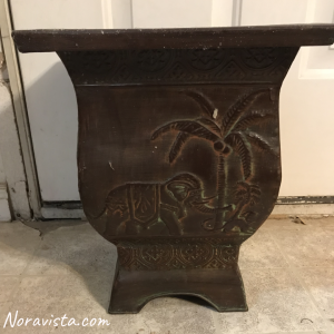A metal bohemian planter with an elephant and monkey on the sides