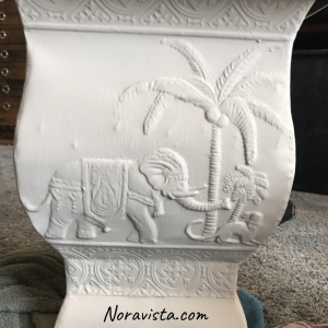 A beige painted metal bohemian planter with an elephant and monkey on the sides.