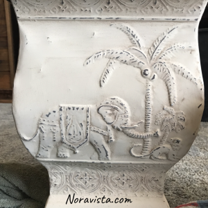 A beige painted metal bohemian planter with an elephant and monkey on the sides and sanded through for distressing look