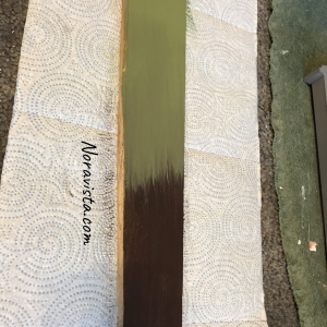 A green and brown painted piece of wood