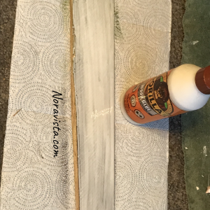 A piece of wood with glue brushed over the entire piece and Gorilla Glue in the background