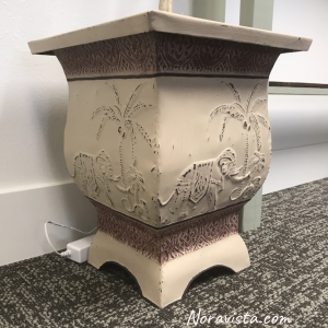 A bohemian planter with an elephant, monkey and a palm tree on each of the four panels, painted beige, dark red and dark purple with distressing