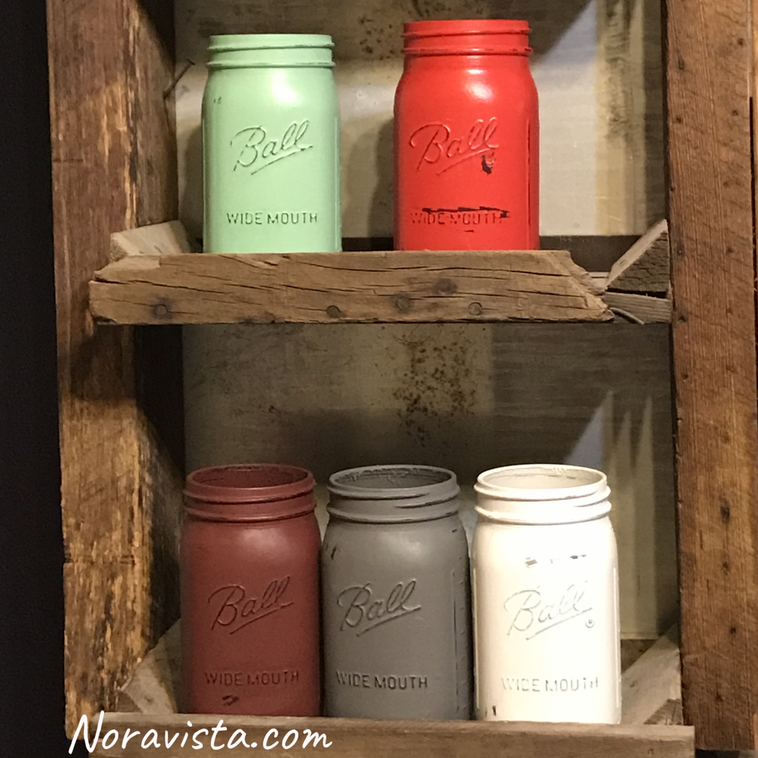 Painted mason jars in teal, red, rusty red, gray and white sitting on a reclaimed wood shelf