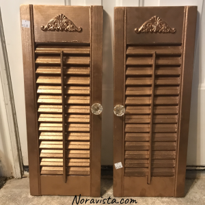Mini shutters spray painted a shimmering gold with a decorative emblem at the top