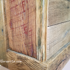 A close up view of a reclaimed oak barn wood apothecary cabinet with original red barn paint and saw tooth marks on the sides, and the molding on the vertical front and back, and horizontal molding.