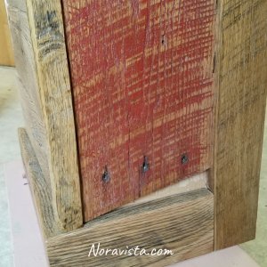 A close up view of a reclaimed oak barn wood apothecary cabinet with original red barn paint and saw tooth marks on the sides with old nail holes and a gap at the bottom, and the molding on the vertical front and back, and horizontal molding.