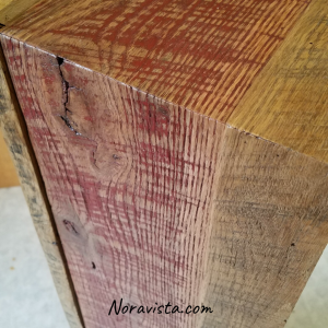 A close up view of the top of a reclaimed oak barn wood apothecary cabinet with a waterfall effect continuing from the top down the side. The top and sides have original red barn paint on them and saw tooth marks