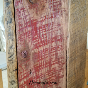 An up close view of a reclaimed oak barn wood apothecary cabinet with original red barn paint and saw tooth marks