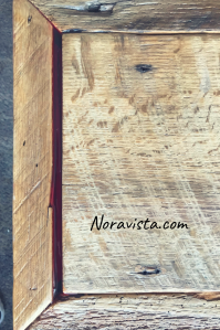 A reclaimed oak barn wood branch top with red epoxy in a crevice between the end molding and the top board