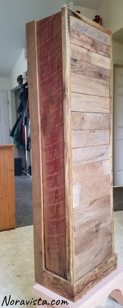 A reclaimed oak barn wood apothecary cabinet with original red barn paint on the sides and top