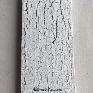 A whit crackled painted piece of wood