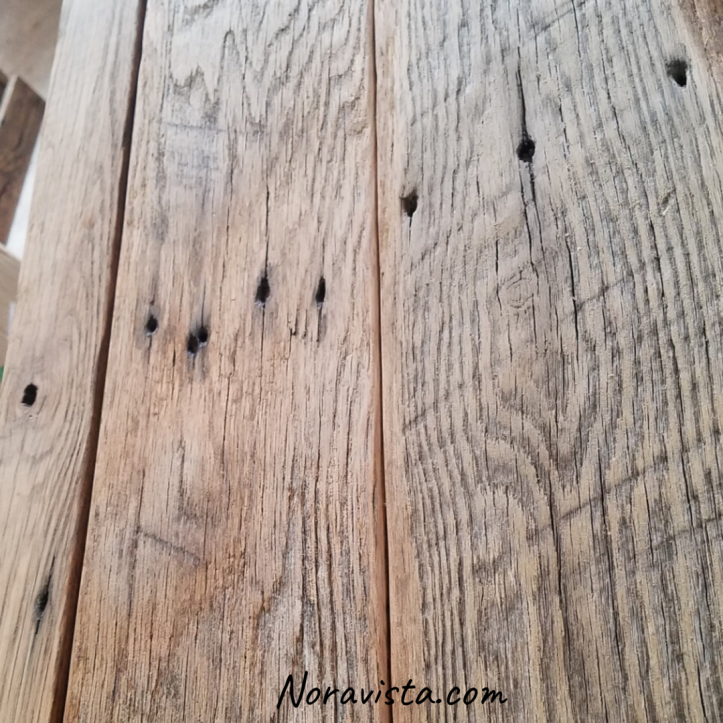 Reclaimed oak barn wood layed up next to each other with a close up view of old nail holes, cathedral grain and saw tooth marks
