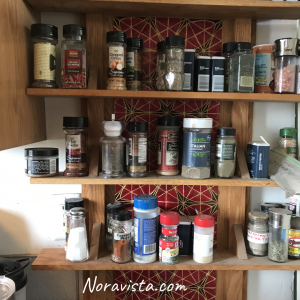 A spice rack with lots of bottles filled with cooking spices and the background of the rack is a canvas art piece with black, red and gold