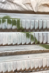 Mini shutters painted a chippy white with a strip of mossy green painted over it