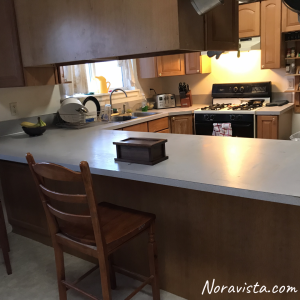 A clean kitchen with laminate countertops and builders grade cabinets