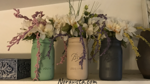 Three painted mason jars in teal, beige and dark gray with silk dahlia and amaranth flowers