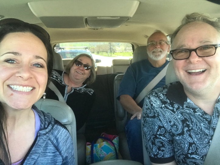 Four people in a car ready for a road trip
