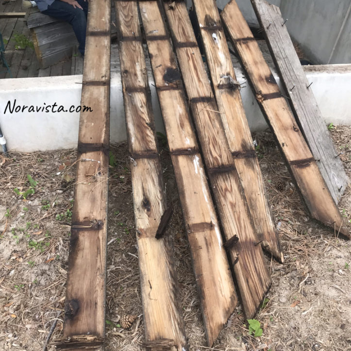 Redwood decking planks that have been pulled up and are drying in the sun with the original nails still in them and rotting wood attached to the original nails