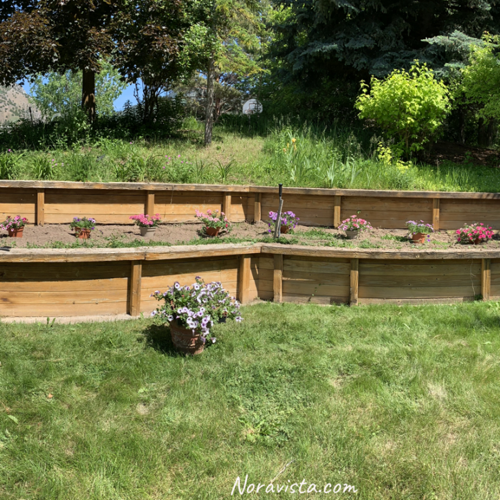 A landscaped garden hillside with flowers in pots ready to be planted