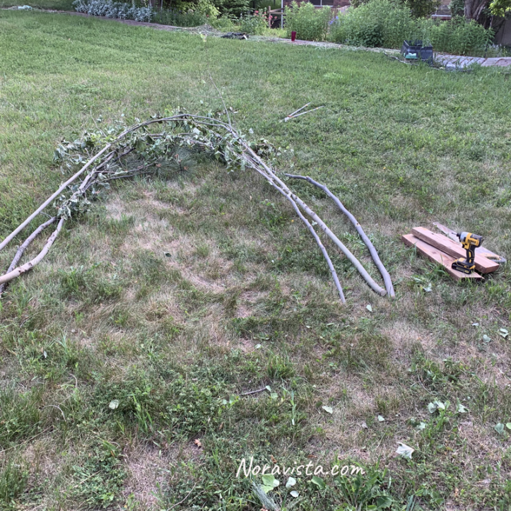 Tree branches layed out in the shape of an arch on the grass next to some 2x4's and a drill