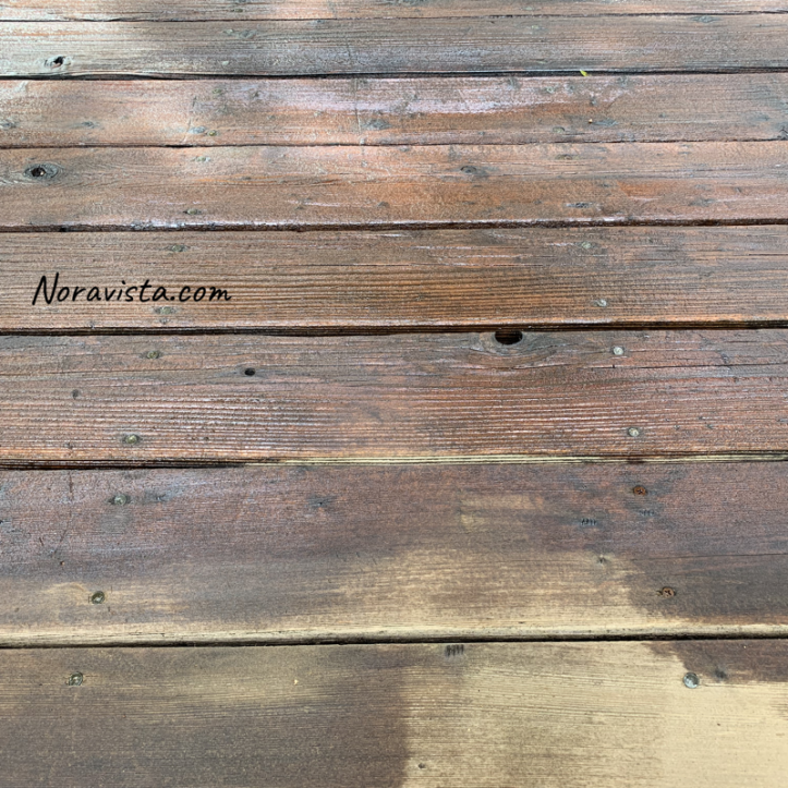 A section of stained redwood decking with a bare spot with no stain on the edge of a plank, between the cracks