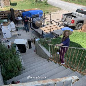 An old gas oven/stove that has been pushed down some exterior stairs and a man and old lady looking at the camera in a cluttered front yard.